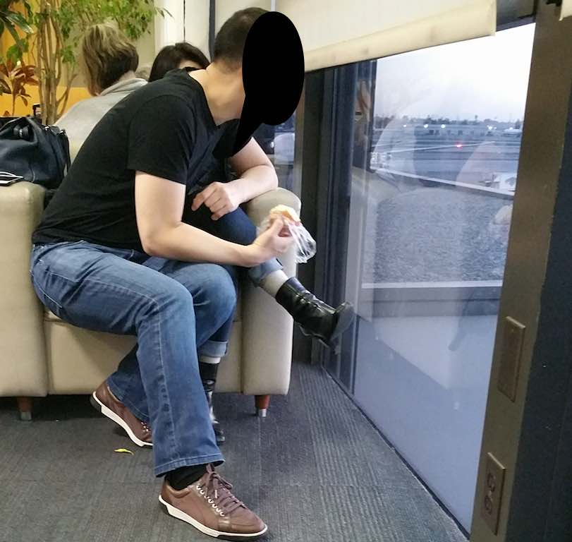 Guy sitting in girlfriend's chair in LAX