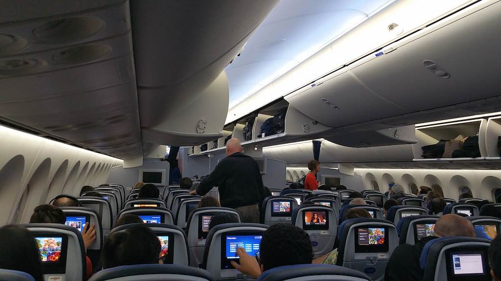 United 1: Economy Class as travelers get settled in. It's a 3-3-3 configuration with mood lighting. The Economy class cabin is divided into Economy Plus and regular Economy